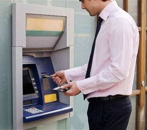 C3JCKG A businessman using a cash machine